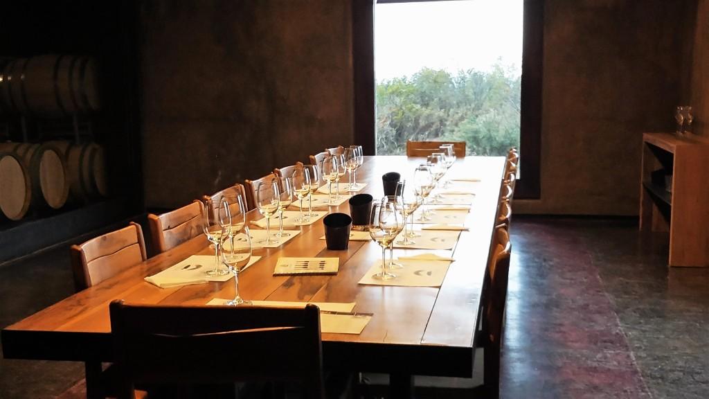 A grande mesa de madeira da sala de degustação da bodega, com as barricas de carvalho ao fundo