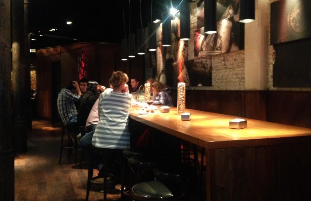 A grande mesa de madeira compartilhada pelos clientes é um dos charmes do bar