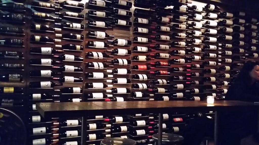 Na parede: nessa parte da adega que não é refrigerada, os vinhos são expostos como se estivessem numa biblioteca