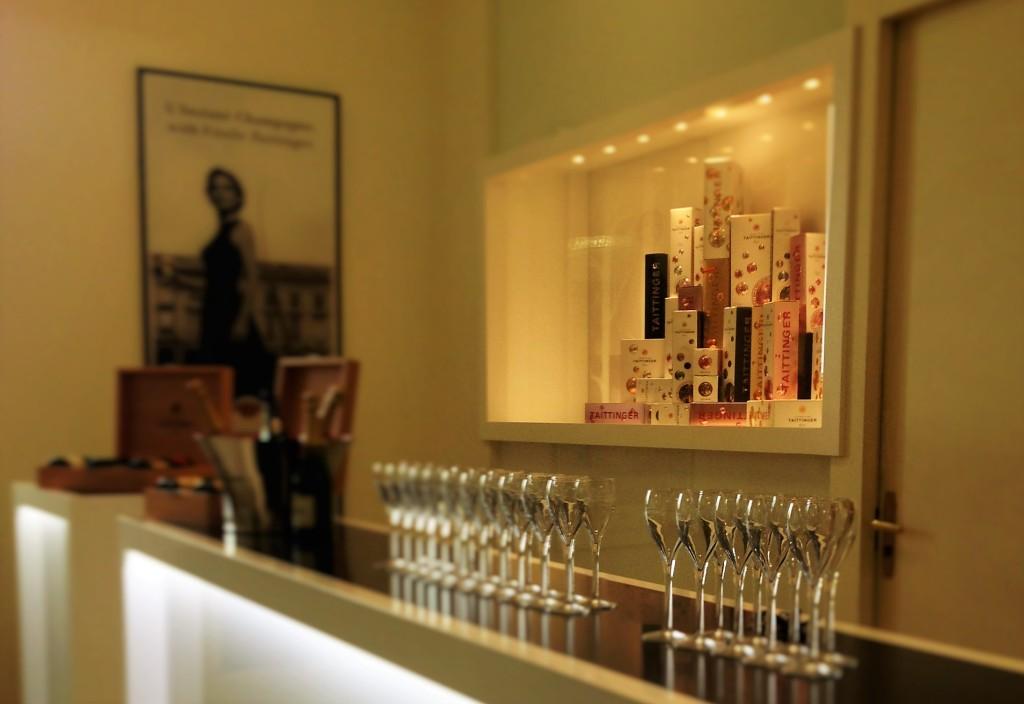 Taças prontas no balcão para mais uma degustação e, ao fundo, embalagens de algumas das 10 linhas de champanhe da Taittinger