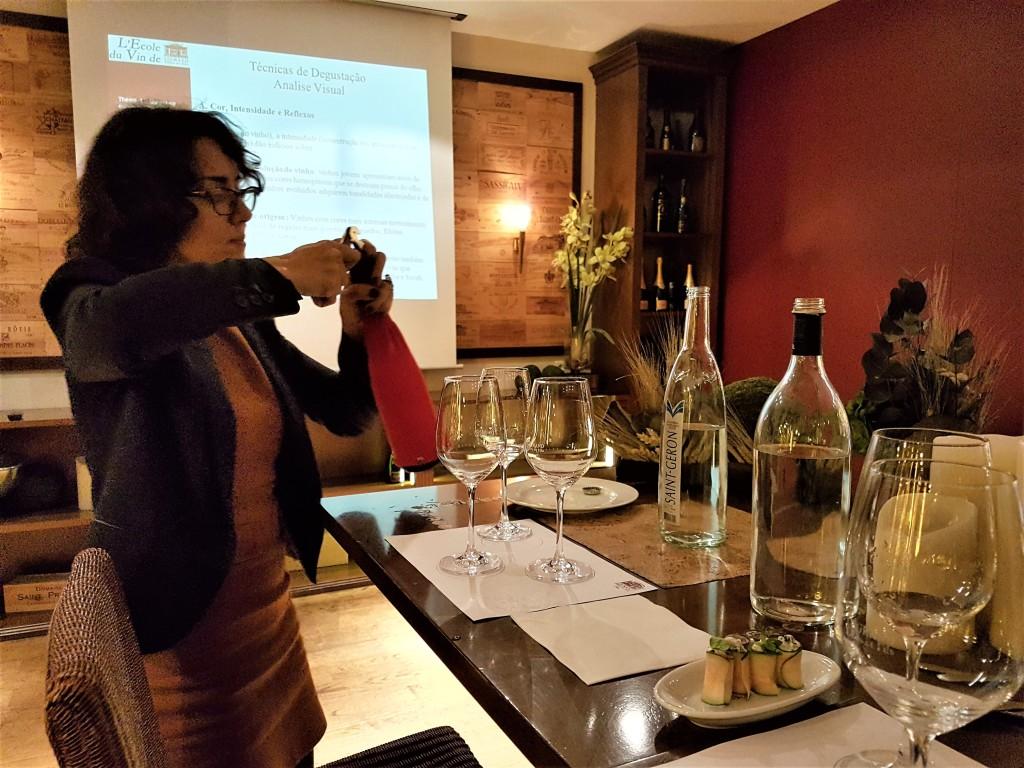 Ana Carolina e uma garrafa coberta dá início à degustação na Cave Legrand: prova às cegas