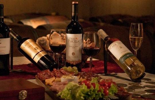 Na cave, degustação de vinhos com queijos e frios