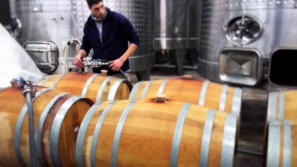Funcionário da vinícola abastecendo uma barrica de carvalho
