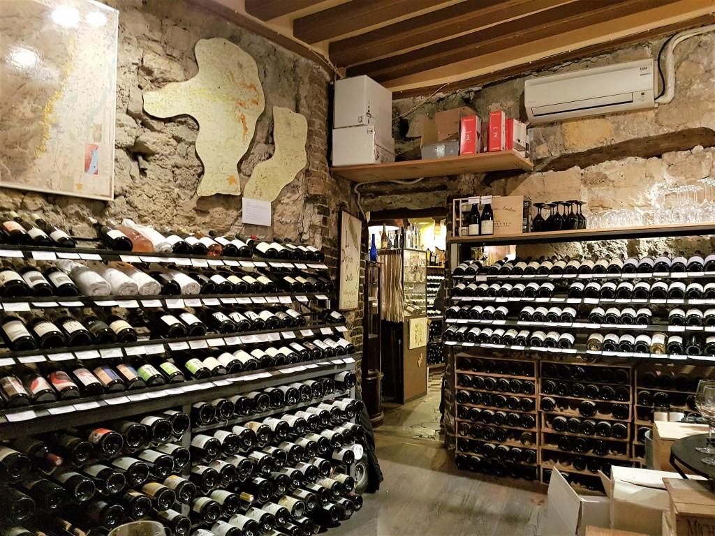O interior da 'La Dernière' com suas paredes de pedras e prateleiras cheias: atmosfera ideal para aprender sobre (e beber) vinhos